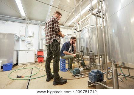 production, business and people concept - men with tablet pc computer and filter compressor at craft beer brewery or non-alcoholic beverage plant
