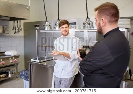 cooking, profession and people concept - happy male chef and cook having coffee break and talking at restaurant kitchen