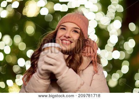 winter holidays, hot drinks and people concept - happy young woman with coffee over christmas tree lights outdoors