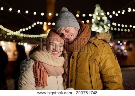 winter holidays and people concept - happy young couple dating and hugging at christmas market in evening