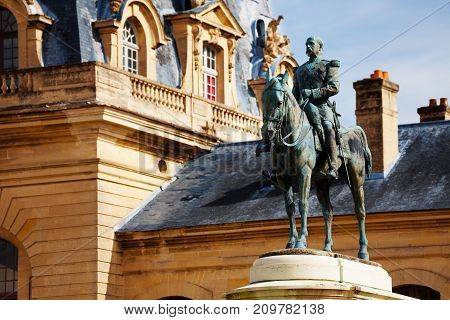 Monument to Henri d'Orleans, the Duke of Aumale against Great Stables building, Chateau de Chantilly, France poster
