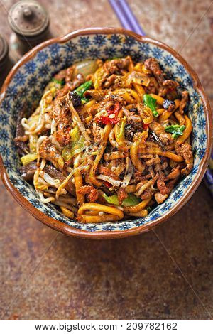 Shanghai beef noodles. Udon noodles with wok fried marinated beef strips in soy sauce with pak choi and red chillies