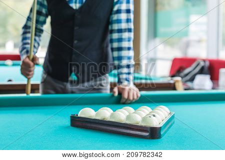 The collected pyramid of balls on the green table cloth in the triangle on the table with the player's cue