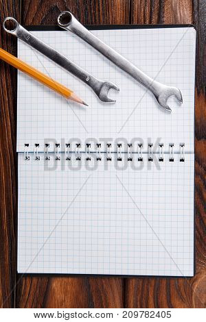 Vertical photo of old hand tools and notepad on wooden table