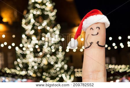 holidays and body parts concept - close up of one finger with smiley in santa hat over christmas tree lights background