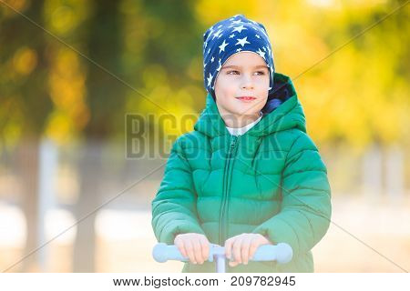 Photo child on a bicycle at asphalt road in the park