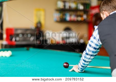 The player in the checkered shirt is going to break the pyramid with a red ball
