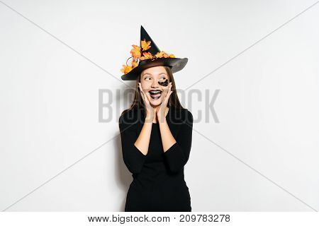 young sexy gothic girl dressed in a witch for halloween, standing in a big black hat, adorned with yellow leaves, laughs