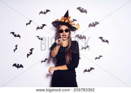 young sexy gothic girl dressed in a witch for a halloween, in a big black hat and sunglasses, points her finger at the camera