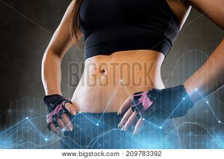 sport, fitness, bodybuilding, sportswear and people concept - young woman body in gym