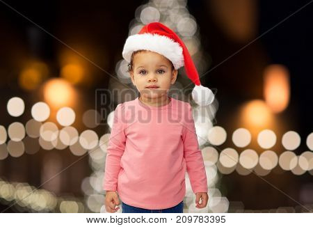 holidays and people concept - little baby girl in santa hat over christmas tree lights background