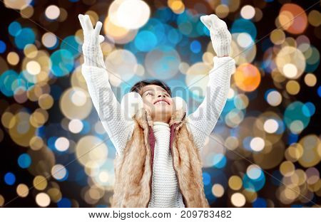 winter, christmas and people concept - happy little girl wearing earmuffs and gloves over holidays lights background