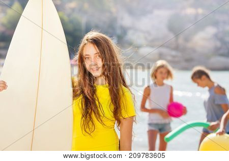 Cute teenage girl standing with surf board on sunlit beach and her friends chatting behind