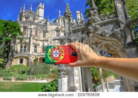 Tourism and travel concept in Europe.Closeup of mobile phone with Portugal flag cover taking photos of popular tourist attractions i the historic city of Sintra, Lisbon district. Defocused background.