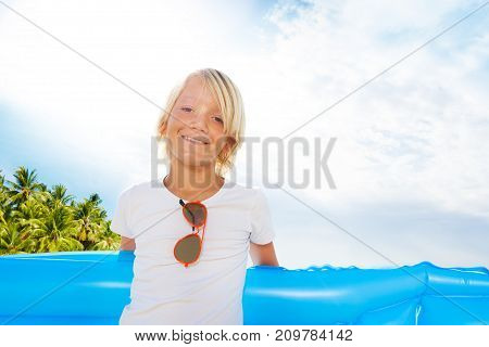 Portrait of blond little boy with sunglasses smiling and looking at camera