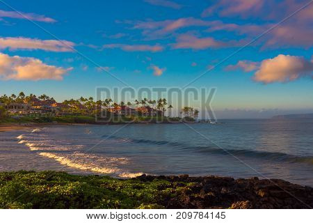 The golden sun of late afternoon lights a beach in Maui Hawaii as waves roll gently in to shore.