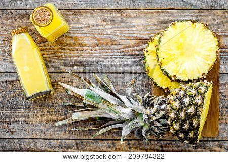 Tropical fruits juice. Bottle with beverage near pineapples slices on wooden background top view.