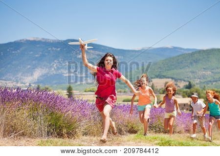 Running kids harry after girl with toy plane in lavender meadow