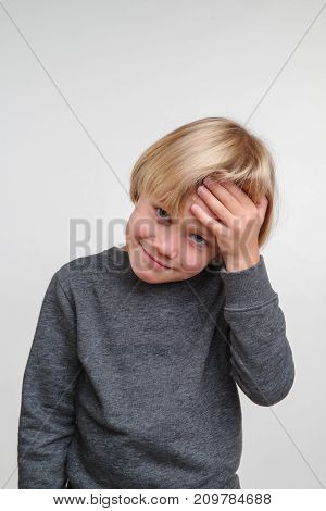 Vertical photo of emotional caucasian boy. Handsome happy child, image on grey background