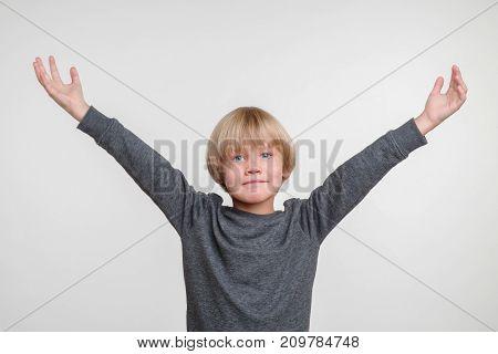 Horisontal emotional portrait of caucasian boy. Handsome happy child, photo on grey background