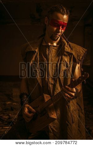 Post-apocalyptic guitarist playing the guitar in a abandoned building