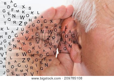 Mature Man Holding Hand Near Ear And Listening Carefully Alphabet Letters Fly