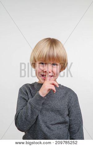Vertical portrait of handsome happy child, photo on grey background