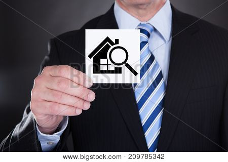 Close-up Of A Businessman Showing House And Magnifying Glass On Paper