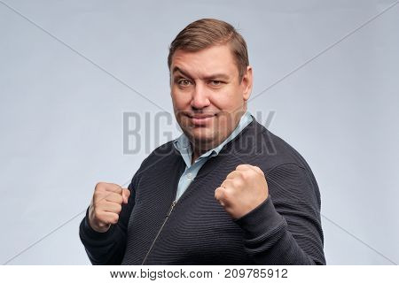 Half body portrait of confident middle aged man with folded arms looking at camera. He is ready to fight