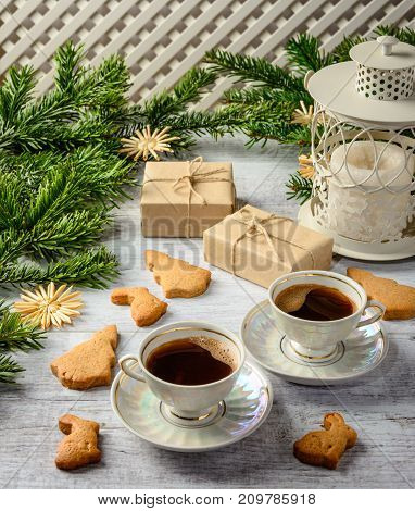 Christmas festive card with fir branches and gift boxestwo cups of coffe and cakes on the white wooden background .