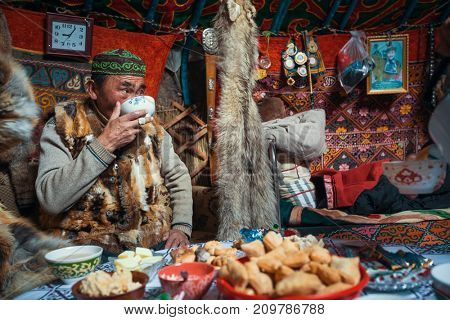 BAYAN-OLGII, MONGOLIA - SEP 28, 2017: Man from Kazakhs family of hunters who hunt with golden eagles inside their the mongolian Yurts. In Bayan-Olgii Province is populated to 88,7% by Kazakhs.