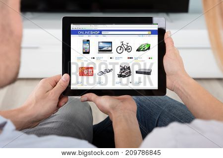 Close-up Of Two People Looking At Online Shopping Website On Digital Tablet