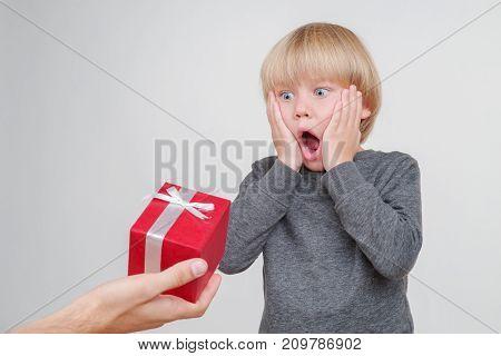 Emotional portrait of caucasian boy isolated on white background vith gift