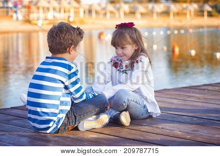 Girl and boy playing on the beach at sunset time. First love. They sit by the lake and have a good time. Unforgettable moments
