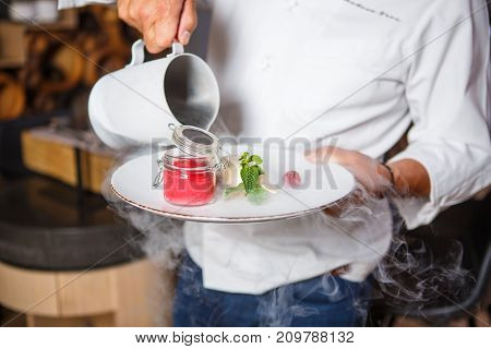 Hands chef holding a white plate with ice cream dessert and pouring from the jug with dry ice