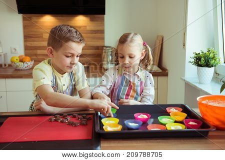 Two Happy Children Baking Christmas Cookies And Muffins At Kitchen