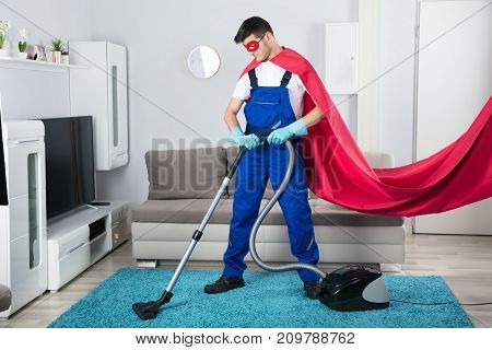 Superhero Janitor Cleaning Carpet With Vacuum Cleaner In Living Room