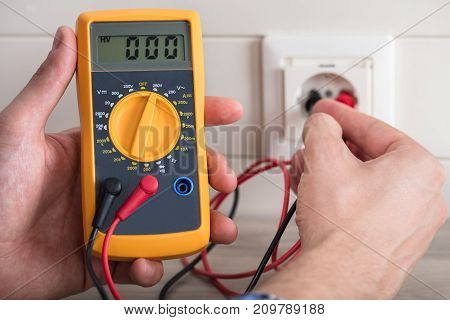 Close-up Of Human Hand And Metering Socket Voltage With Digital Multimeter