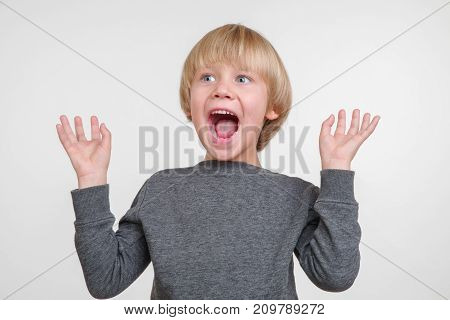 Emotional portrait of angry caucasian small boy
