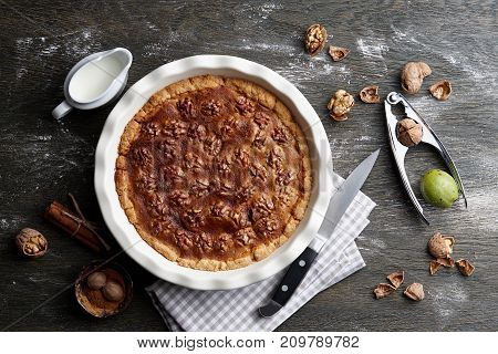 Traditional walnut pie, spices, nuts and nutcracker on dark wooden table, top view