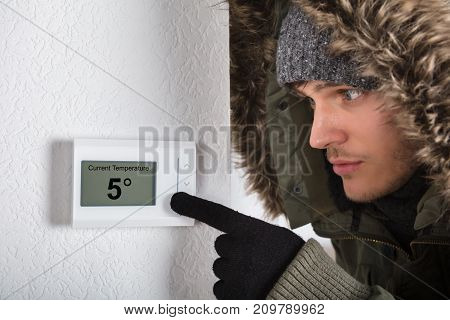 Young Man In Warm Clothing Pointing To Current Room Temperature In Digital Thermostat At Home