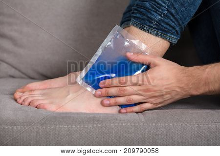 Close-up Of Person's Hand Holding Ice Gel Pack On Ankle At Home