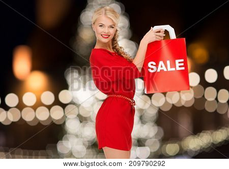 sale, holidays and people concept - smiling woman in red dress with shopping bag over christmas tree lights background