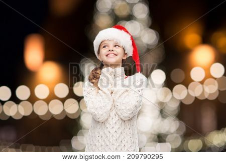 christmas, holidays and people concept - dreaming girl in santa helper hat over lights background