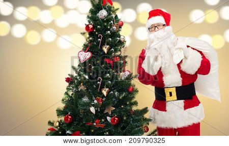 holidays and people concept - man in costume of santa claus with bag and christmas tree making hush gesture