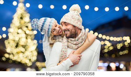 winter, holidays and people concept - happy couple in hats hugging over christmas tree lights background