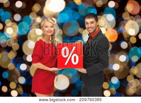 shopping, sale and people concept - happy couple with discount sign over christmas lights background