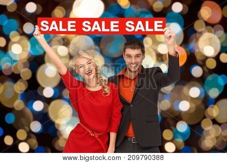 shopping, holidays and people concept - couple with red sale sign over christmas lights background