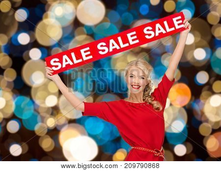 shopping, christmas and people concept - smiling woman in dress with red sale sign over lights background