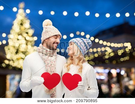 holidays, love and people concept - happy couple in winter hats holding red paper heart shapes over christmas tree lights background